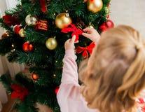 Ciérrese para arriba del niño que adorna el árbol de navidad Fotos de archivo