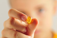 Ciérrese para arriba del niño que sostiene la píldora amarilla Fotos de archivo