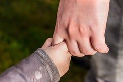 Ciérrese para arriba del padre que lleva a cabo la mano del niño Fotos de archivo