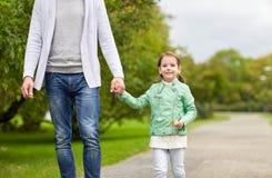 Ciérrese para arriba del padre y de la niña que caminan en parque Fotos de archivo