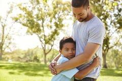 Ciérrese para arriba del parque de Hugging Son In del padre imagenes de archivo