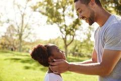 Ciérrese para arriba del parque de Kissing Daughter In del padre imagen de archivo libre de regalías