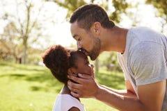 Ciérrese para arriba del parque de Kissing Daughter In del padre fotografía de archivo libre de regalías
