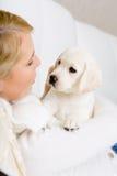 Ciérrese para arriba del perrito blanco del abarcamiento de la mujer Imágenes de archivo libres de regalías