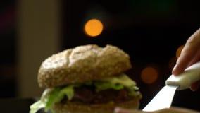 Ciérrese para arriba del proceso de cocinar una hamburguesa en una cocina abierta de los alimentos de preparación rápida tarde Bo almacen de video