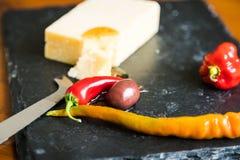 Ciérrese para arriba del queso cheddar, de la pimienta roja y de la aceituna en pizarra Imágenes de archivo libres de regalías