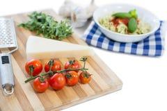 ciérrese para arriba del queso y de los tomates en tabla de cortar Fotos de archivo