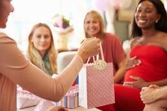 Ciérrese para arriba del regalo para la mujer embarazada en la fiesta de bienvenida al bebé fotografía de archivo