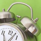 Ciérrese para arriba del reloj de alarma en un fondo vibrante Imagenes de archivo
