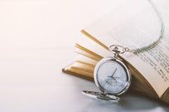 Ciérrese para arriba del reloj de bolsillo de plata antiguo y del libro abierto Fotos de archivo libres de regalías
