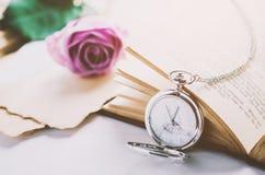 Ciérrese para arriba del reloj de bolsillo de plata antiguo y del libro abierto Foto de archivo