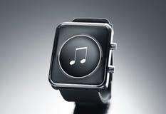 Ciérrese para arriba del reloj elegante negro con el icono de la nota de la música Fotografía de archivo