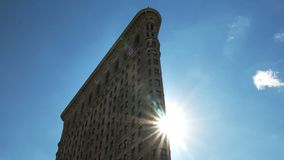 Ciérrese para arriba del sol detrás del edificio de la plancha