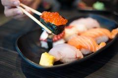 Ciérrese para arriba del suhi de Ikura en palillos y conjunto del sushi de la variedad Fotografía de archivo libre de regalías