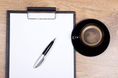 Ciérrese para arriba del tablero, de la pluma y de la taza en blanco de café sólo en la madera Foto de archivo