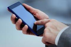 Ciérrese para arriba del teléfono de célula de tenencia de las manos del ` s de las mujeres con el pedregal en blanco del espacio Imagen de archivo libre de regalías