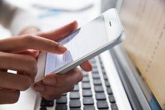 Ciérrese para arriba del teléfono de Person At Laptop Using Mobile imagen de archivo libre de regalías