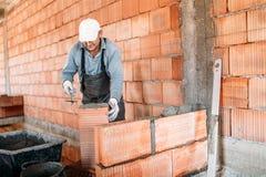 Ciérrese para arriba del trabajador industrial, albañil que instala ladrillos en el edificio interior en el emplazamiento de la o fotos de archivo
