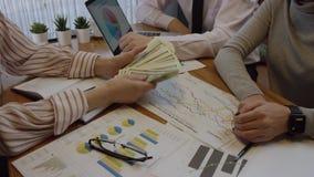 Ciérrese para arriba del trabajo con los documentos y de contar el dinero Tres personas están trabajando juntas y están discutien almacen de video