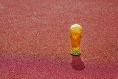 Ciérrese para arriba del trofeo de oro falso bajo la forma de globo sobre un material reciclado plástico rojo en al aire libre Fotografía de archivo libre de regalías