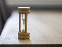 Ciérrese para arriba del vidrio de madera de la hora en la tabla foto de archivo libre de regalías
