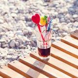 Ciérrese para arriba del vidrio del cóctel alcohólico que se coloca en la arena en una playa tropical Fotos de archivo libres de regalías