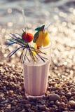 Ciérrese para arriba del vidrio del cóctel alcohólico que se coloca en la arena en una playa tropical Fotografía de archivo libre de regalías