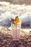 Ciérrese para arriba del vidrio del cóctel alcohólico que se coloca en la arena en una playa tropical Imagen de archivo