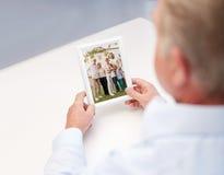 Ciérrese para arriba del viejo hombre que sostiene la foto de familia feliz Imágenes de archivo libres de regalías