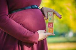 Ciérrese para arriba del vientre embarazada con el nombre del bebé encendido Foto de archivo