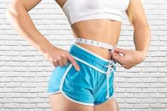 Ciérrese para arriba del vientre entrenado con la cinta métrica Foto de archivo libre de regalías