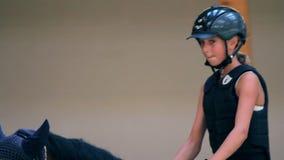 Ciérrese para arriba en caballo de montar a caballo de la chica joven almacen de video
