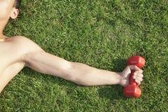 Ciérrese para arriba en el brazo y lleve a hombros llevar a cabo la pesa de gimnasia roja en hierba, visión desde arriba Imágenes de archivo libres de regalías