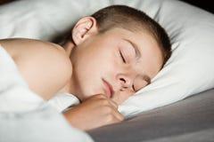 Ciérrese para arriba en el muchacho dormido en cama Imagen de archivo libre de regalías