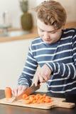Ciérrese para arriba en el niño que corta cuidadosamente zanahorias Foto de archivo libre de regalías