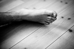 Ciérrese para arriba en el pie masculino sobre piso de madera fotografía de archivo libre de regalías