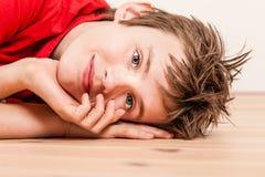 Ciérrese para arriba en la cabeza del muchacho feliz que miente en piso Imagen de archivo libre de regalías