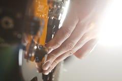 Ciérrese para arriba en la mano del ` s del hombre que toca la guitarra Foto de archivo
