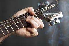 Ciérrese para arriba en la mano del ` s del hombre que toca la guitarra Fotos de archivo