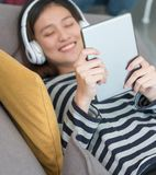 Ciérrese para arriba en la tableta con el adolescente que disfruta de escuchar Foto de archivo libre de regalías