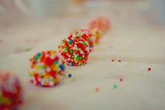 Ciérrese para arriba en las bolas blancas del chocolate cubiertas con los caramelos dispuestos en fila Imágenes de archivo libres de regalías