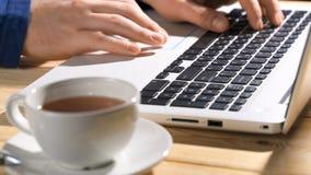 Ciérrese para arriba en las manos del hombre anónimo que trabajan en el ordenador portátil con la taza del té caliente, foco en l metrajes