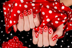 Ciérrese para arriba en las manos femeninas hermosas con la manicura roja linda con los puntos blancos. Fotografía de archivo