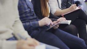 Ciérrese para arriba en los empleados en la reunión que anotan notas tiro del steadycam almacen de metraje de vídeo