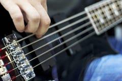 Ciérrese para arriba en los fingeres del músico que tocan la guitarra baja en la etapa Fotos de archivo libres de regalías