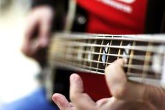 Ciérrese para arriba en los fingeres del músico que tocan la guitarra baja en la etapa Imagenes de archivo