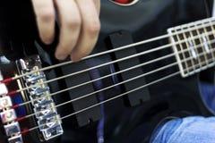Ciérrese para arriba en los fingeres del músico que tocan la guitarra baja en la etapa Foto de archivo libre de regalías
