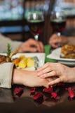 Ciérrese para arriba en los pares que llevan a cabo las manos durante cena Imagen de archivo libre de regalías