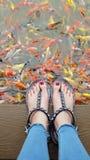 Ciérrese para arriba en los pies del ` s de la muchacha que llevan las sandalias de plata y los clavos rojos con la natación de l Foto de archivo