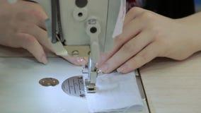 Ciérrese para arriba en una máquina de coser que muestra proceso almacen de metraje de vídeo
